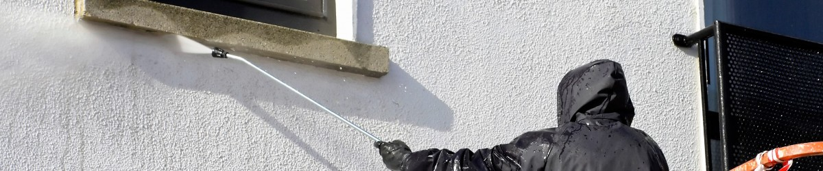 worker in cherry-piker washing a wall